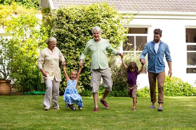 Gelukkige familie die op gras in werf geniet van