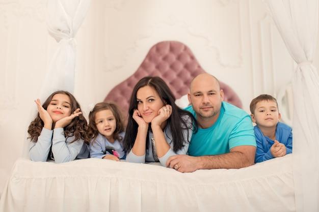 Gelukkige familie die op het bed voor de gek houdt. geniet van de tijd met dierbaren.