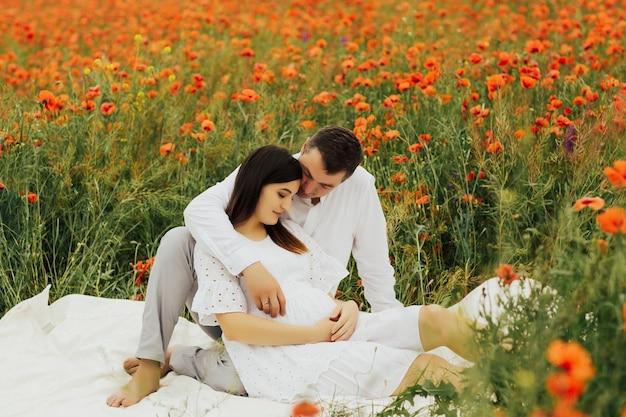 Gelukkige familie die op het papavergebied rust Premium Foto