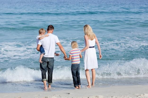Gelukkige familie die op het zand loopt