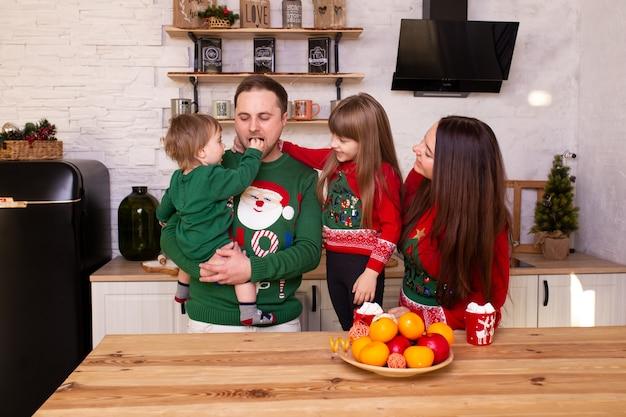Gelukkige familie die op kerstmis thuis in keuken wacht
