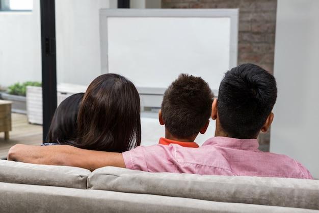 Gelukkige familie die op tv op de bank let