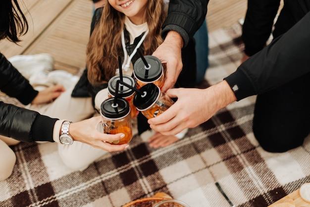 Gelukkige familie die picknickhanden hebben die glazen met de herfstpicknick van rietjes houden