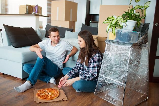 Gelukkige familie die pizza op bewegende dag eet. beeld van een jong paar dat van rusttijd geniet terwijl samen het zitten in het nieuwe huis.