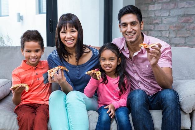 Gelukkige familie die pizza op de bank eet