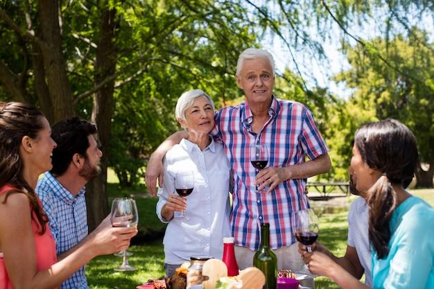 Gelukkige familie die rode wijn in park heeft