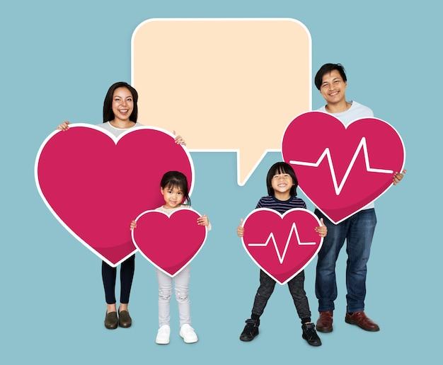 Gelukkige familie die roze hartpictogrammen houden