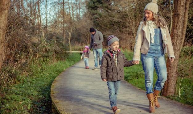 Gelukkige familie die samen hand in hand loopt over een houten pad naar het bos