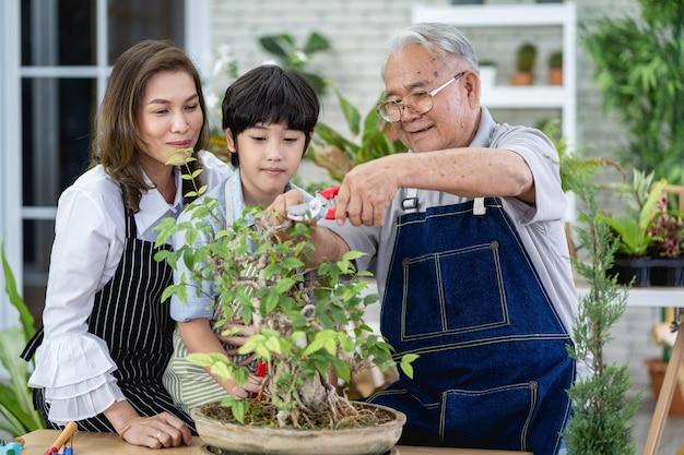 Gelukkige familie die samen in de tuin tuiniert, grootvader kleinzoon en vrouw die voor de natuur zorgen