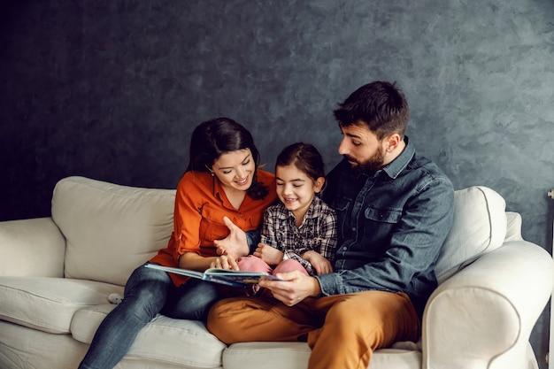 Gelukkige familie die samen zitten en samen quality time hebben. vader leest een sprookje voor aan zijn geliefde dochter.