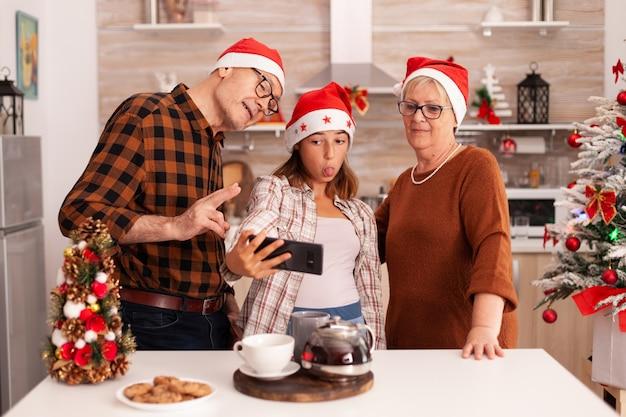 Gelukkige familie die selfie maakt met telefoon en grappige uitdrukkingen maakt tijdens de foto