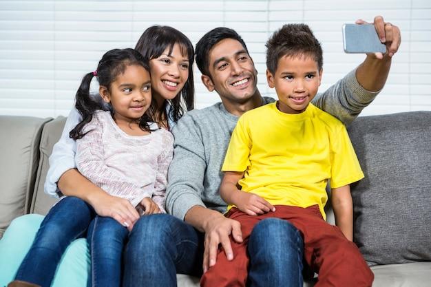 Gelukkige familie die selfie op bank nemen