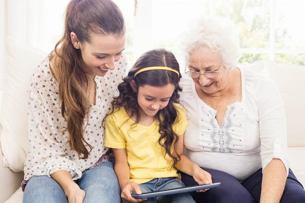 Gelukkige familie die tablet thuis gebruikt