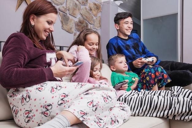 Gelukkige familie die technologieën op bank gebruiken