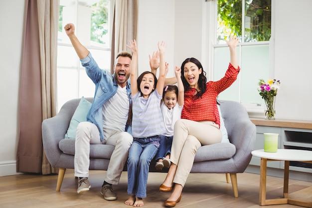 Gelukkige familie die terwijl het situeren op bank toejuicht