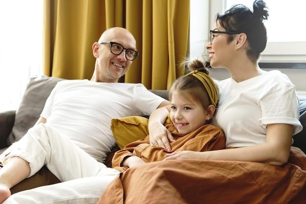 Gelukkige familie die thuis op de bank zit en ontspant
