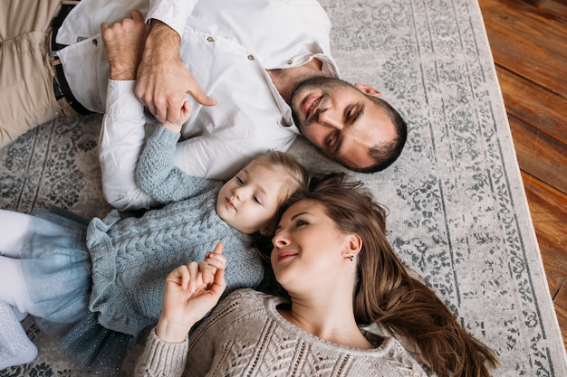 Gelukkige familie die thuis op de vloer ligt. bovenaanzicht