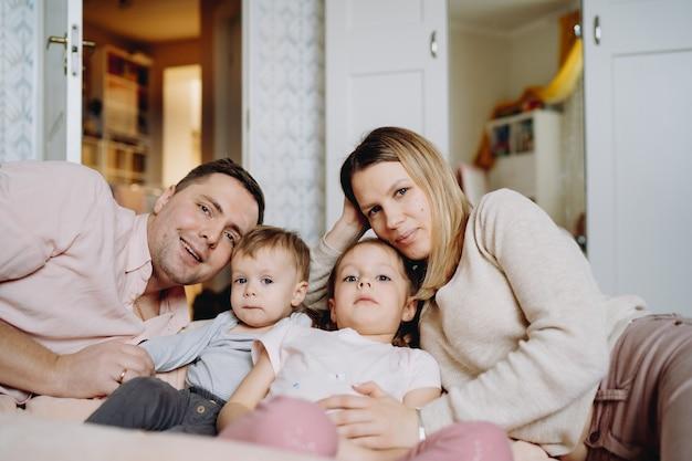 Gelukkige familie die thuis plezier heeft en hun kinderen knuffelt die op de vloer liggen in de kinderkamer
