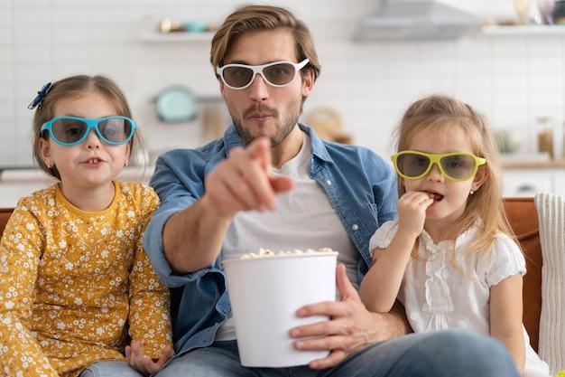 Gelukkige familie die thuis tv kijkt en popcorn eet.
