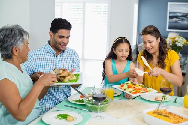 Gelukkige familie die van meerdere generaties maaltijd op lijst heeft