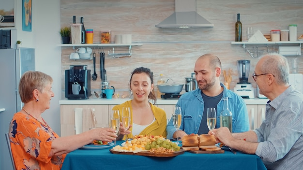 Gelukkige familie die verjaardag viert en samen geniet van het maken van gejuich met witte wijn. meerdere generaties, vier mensen, twee gelukkige koppels die praten en eten tijdens een gastronomisch diner, genietend van de tijd thuis