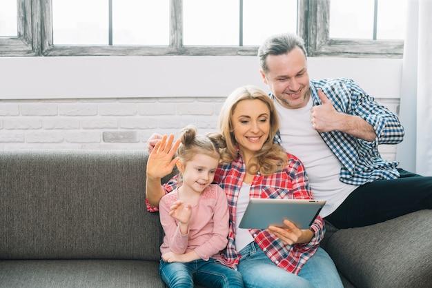 Gelukkige familie die videovraag op digitale tablet maken