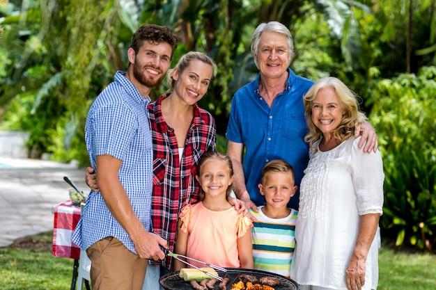Gelukkige familie die voedsel in barbecue roostert bij werf