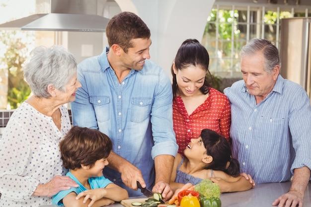 Gelukkige familie die voedsel in keuken voorbereidt
