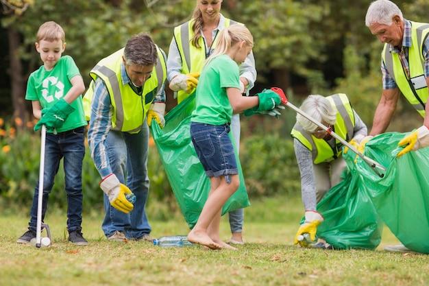 Gelukkige familie die vuilnis verzamelt