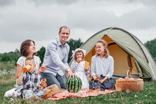 Gelukkige familie die watermeloen eet bij picknick in weide dichtbij de tent. familie genieten van kampeervakantie op het platteland