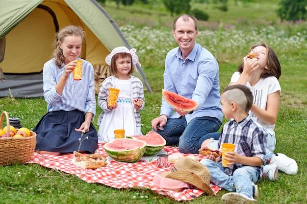 Gelukkige familie die watermeloen eet bij picknick in weide dichtbij de tent. familie genieten van kampeervakantie op het platteland.