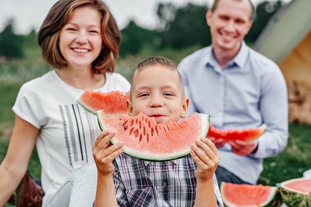 Gelukkige familie die watermeloen eet bij picknick in weide dichtbij de tent. moeder, vader en kind genieten van kampeervakantie op het platteland