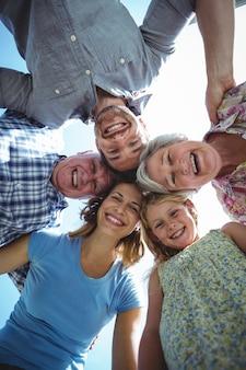 Gelukkige familie die wirwar vormen tegen hemel