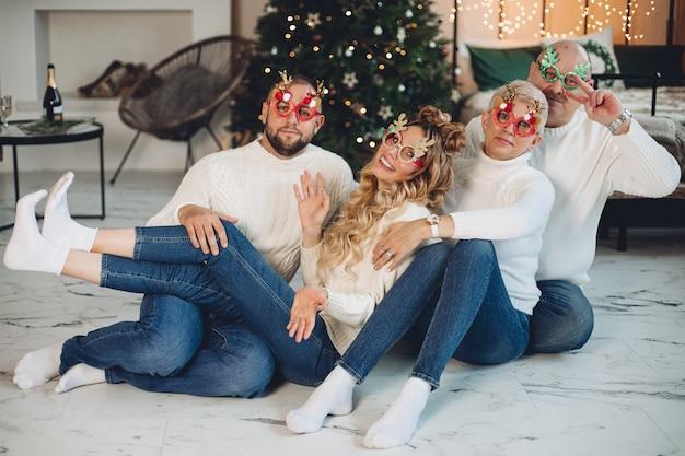 Gelukkige familie die witte truien draagt en plezier heeft tijdens het samen vieren van het nieuwe jaar