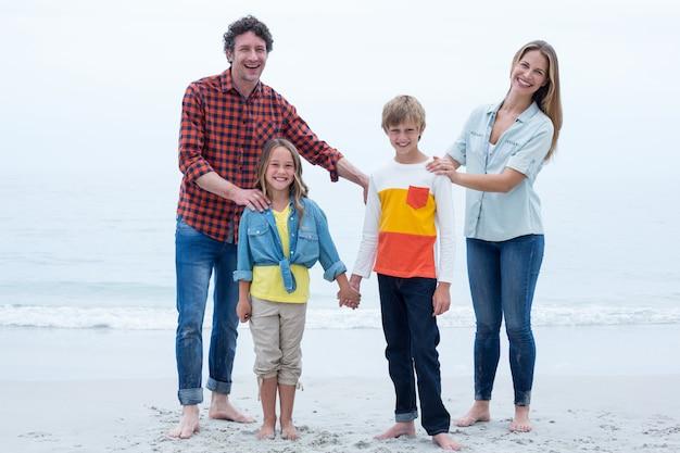 Gelukkige familie die zich op zee kust tegen hemel bevindt