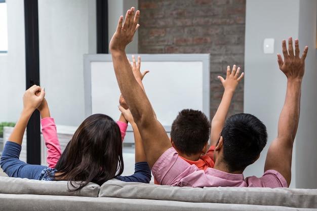 Gelukkige familie die zich terwijl het letten van op tv op de bank verheugt