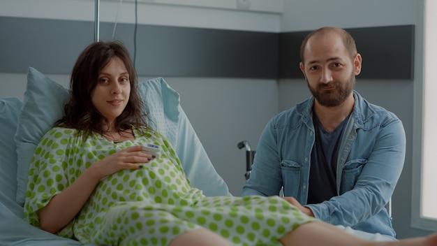 Gelukkige familie die zich voorbereidt op de bevalling in de ziekenhuisafdeling
