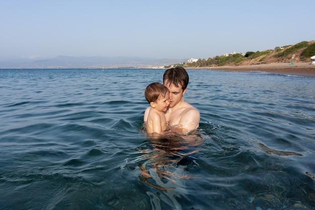 Gelukkige familie en gezonde levensstijl. een jonge vader leert een kind zwemmen in de zee