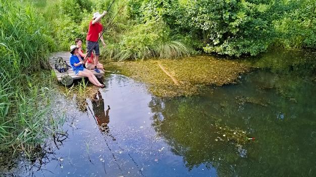 Gelukkige familie en vrienden die samen in openlucht dichtbij meer in de zomer vissen, lucht hoogste mening van hierboven