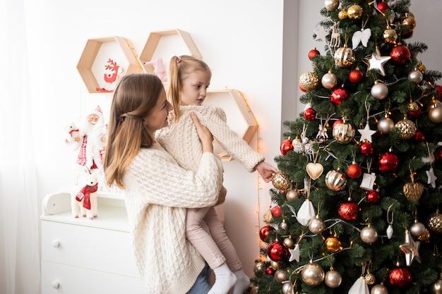 Gelukkige familie familie moeder en kind thuis in de buurt van de kerstboom