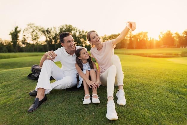 Gelukkige familie geniet van de zomer natuur neemt foto.
