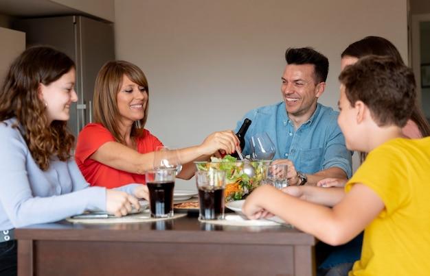 Gelukkige familie genieten van lunch samen thuis enjoying