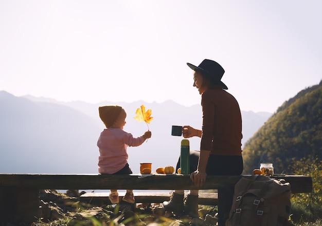 Gelukkige familie genieten van vakanties in de herfst. moeder en dochter op een picknick in de bergen. moeder en klein kind meisje buiten ontspannen. avontuurlijke reizen met kinderen, kamperen en wandelen in de natuur.