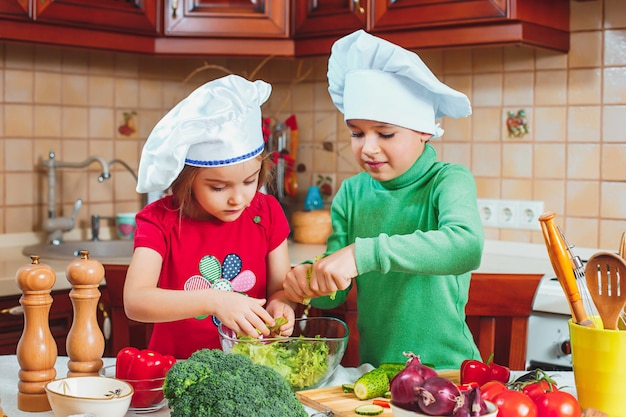 Gelukkige familie grappige kinderen bereiden de verse groentesalade in de keuken voor