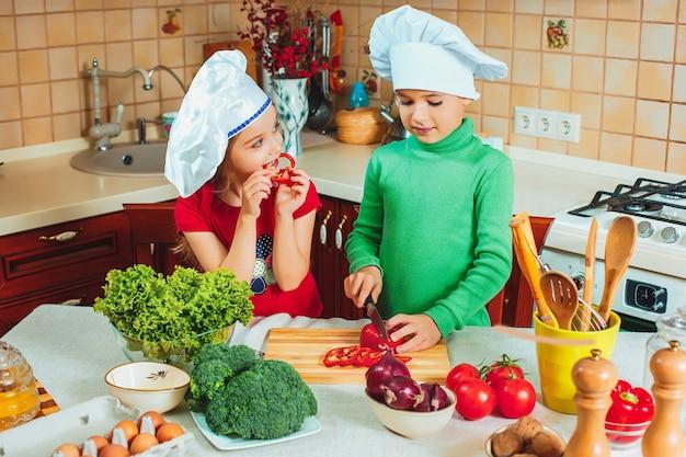 Gelukkige familie grappige kinderen bereiden de verse groentesalade in de keuken