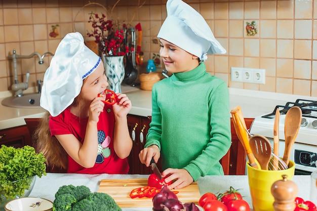 Gelukkige familie grappige kinderen bereiden een verse groentesalade in de keuken