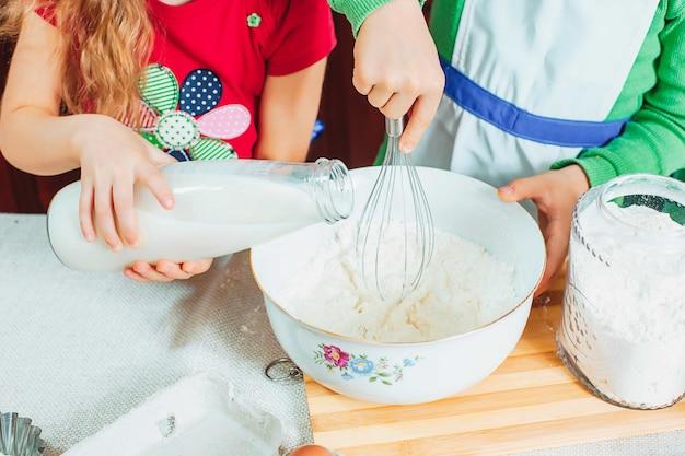 Gelukkige familie grappige kinderen bereiden het deeg voor, bakken koekjes in de keuken
