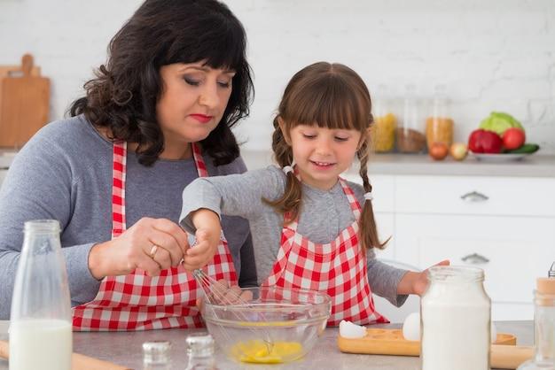 Gelukkige familie grootmoeder en kleine kleindochter in koksschorten die samen in de keuken koken
