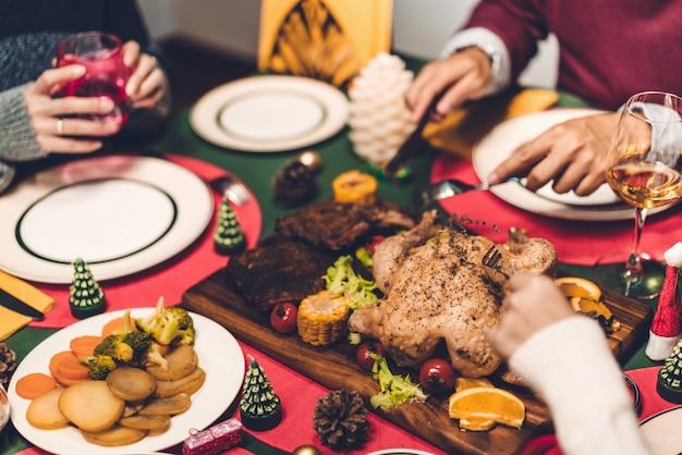 Gelukkige familie hebben diner met smakelijke gebakken geroosterde gehele gebraden kip