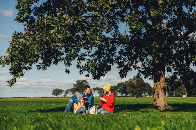 Gelukkige familie hebben herfstpicknick, zitten op groen gras, drinken hete thee, communiceren met elkaar